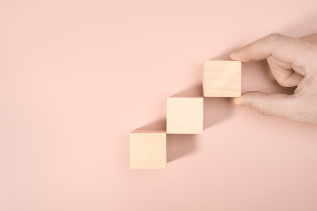 Processus de succès de croissance de concept d'entreprise, close up man hand organiser l'empilement de blocs de bois comme escalier d'étape