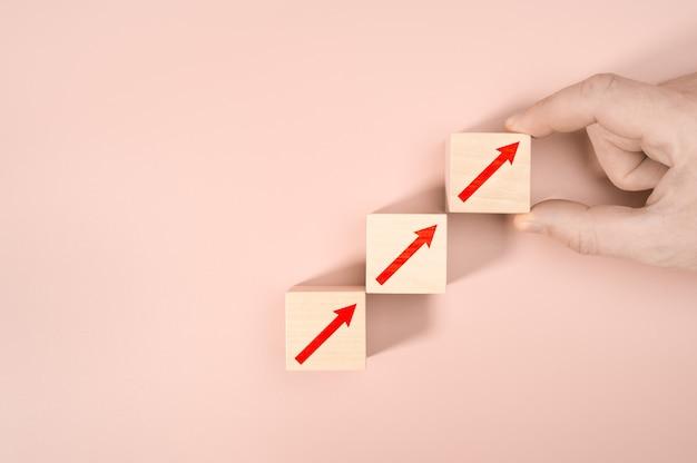 Processus de succès de croissance de concept d'entreprise, gros plan de la main de l'homme organisant l'empilement de blocs de bois