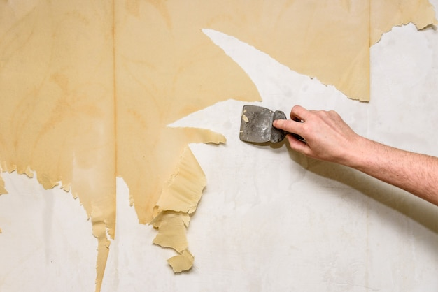 Processus de suppression du vieux papier peint. nettoyage du mur du vieux papier peint humide avec une spatule en métal.