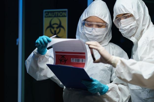 Processus de test du coronavirus: couple scientifique portant un masque médical avec des lunettes de sécurité en combinaison de matières dangereuses, tenant le tube d'échantillons de test sanguin à la main avec des informations sur le test sanguin.