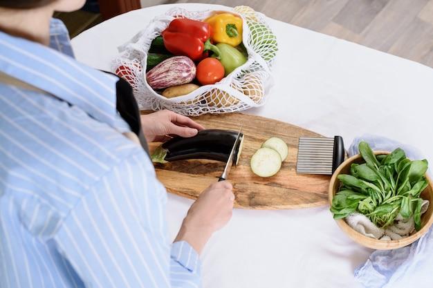 Processus de trancher les aubergines pour moussaka sur planche de bois cuisson à la maison concept