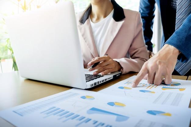 Processus de travail en équipe. les jeunes chefs d'entreprise travaillent avec un nouveau projet de démarrage. ordinateur portable sur table en bois, clavier de saisie, message textuel, analyse des plans graphiques.