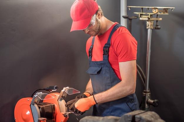 Processus de travail. jeune adulte axé sur l'homme en vêtements de travail et lunettes travaillant près de détail de meulage de machine-outil