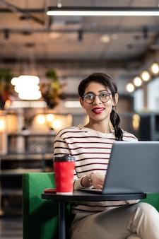 Processus de travail. jolie femme gardant le sourire sur son visage alors qu'elle était assise sur son lieu de travail
