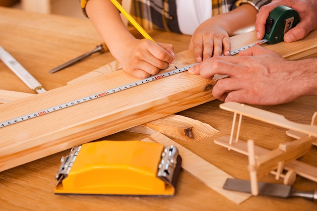 Processus de travail. seriousboy fait des mesures sur la planche de bois pendant que son père l'aide