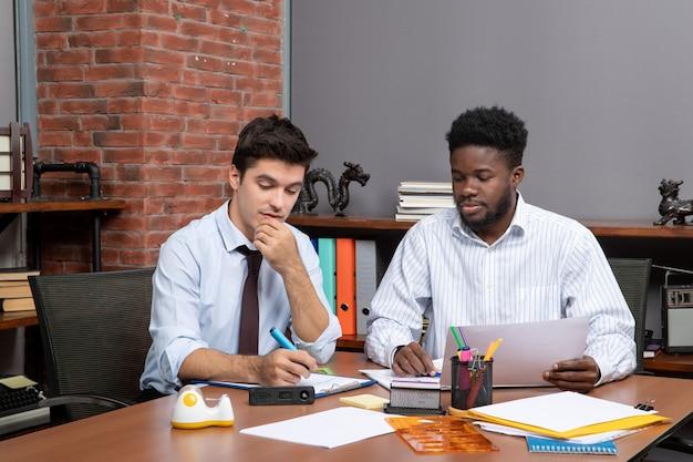 Processus de travail vue de face deux hommes d'affaires assidus travaillant au bureau