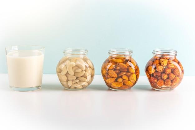 Processus de trempage de diverses noix, amandes, noisettes, noix de cajou dans de l'eau à activer et un verre de lait végétal