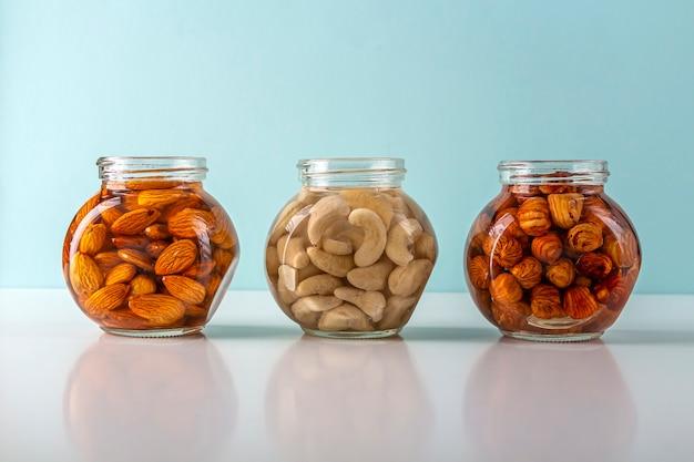 Processus de trempage de diverses noix: amandes, noisettes, noix de cajou dans l'eau dans un bocal en verre pour activer