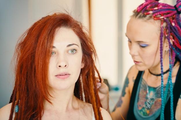 Processus de tressage du maître tisse des tresses sur sa tête dans un salon de beauté