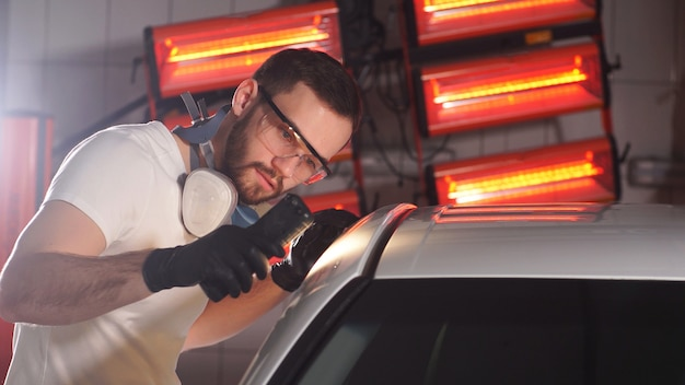 Le processus de vérification de l'application d'un revêtement nanocéramique sur une voiture par un travailleur masculin à l'aide d'une lampe de poche