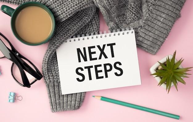 Prochaines étapes écrites sur une carte posée sur la table à côté d'un cahier et d'un stylo