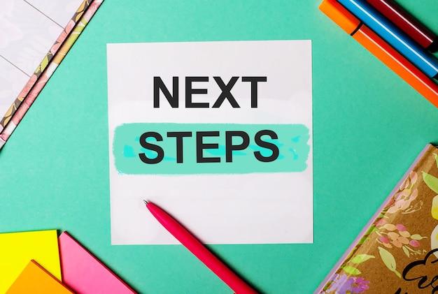 Prochaines étapes écrites sur une surface turquoise à proximité d'autocollants, de blocs-notes et de marqueurs brillants