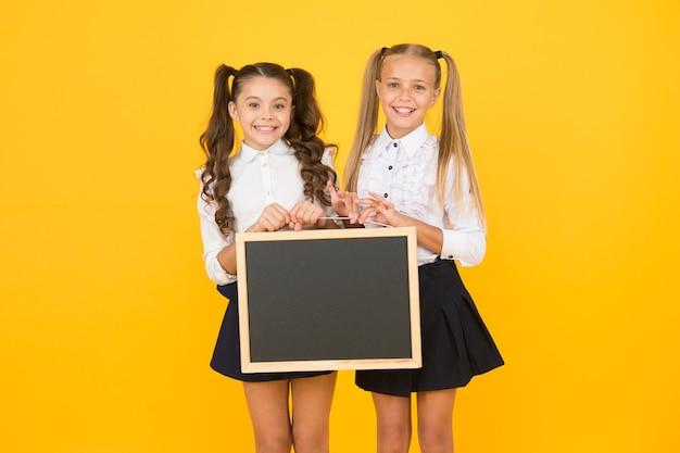 Prochains événements à l'école. heureux d'informer. des écolières vous informent. les écolières tiennent un espace de copie de tableau vierge. communication visuelle. l'uniforme scolaire des filles tient le tableau noir. retour au concept de l'école.
