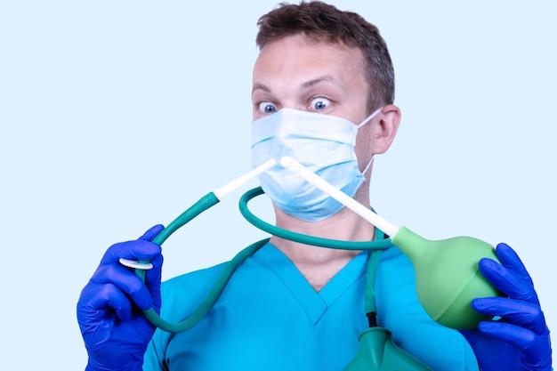 Proctologue, un médecin en vêtements médicaux tient une seringue en caoutchouc
