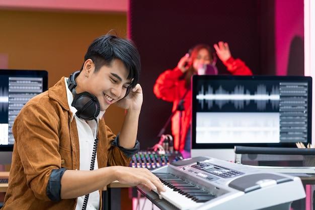 Producteur asiatique debout par console de mixage sonore heureux artiste compositeur de musique masculine