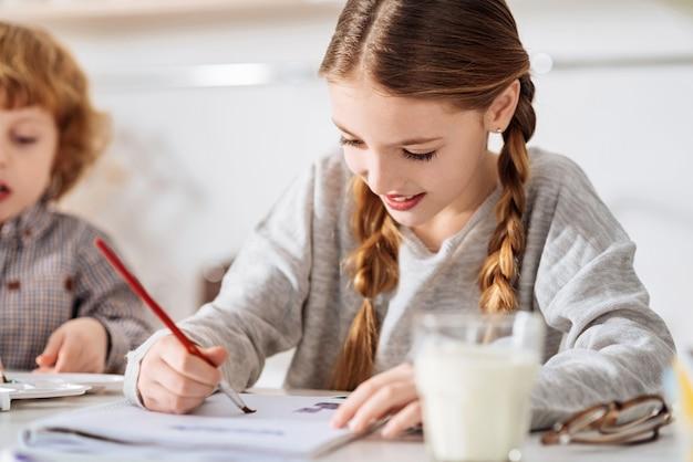 Productif et inspiré. femme ravie artistique motivée dessinant le matin à l'aquarelle en essayant de terminer ses devoirs pendant le week-end