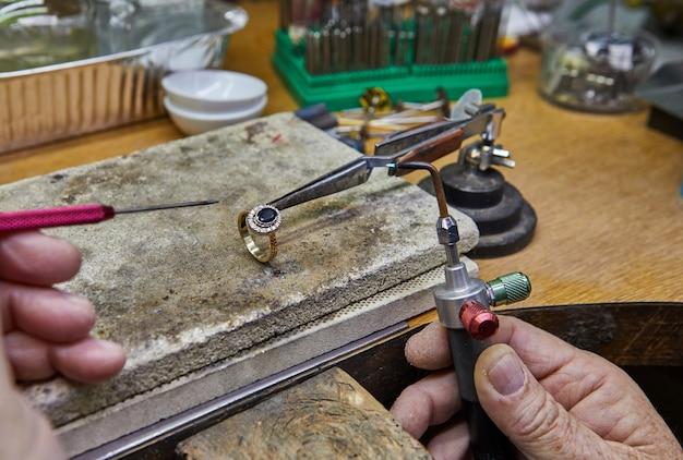 Production de bijoux. le bijoutier fabrique une bague en or.