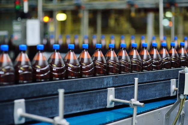Production industrielle alimentaire de bière. bouteilles de bière en plastique sur un tapis roulant dans le contexte d'une brasserie.