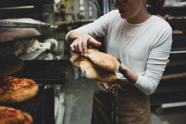 Production de pain cuit au four à bois dans une boulangerie.