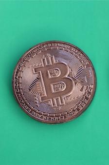 Un produit au chocolat sous forme de bitcoin physique repose sur un fond en plastique vert