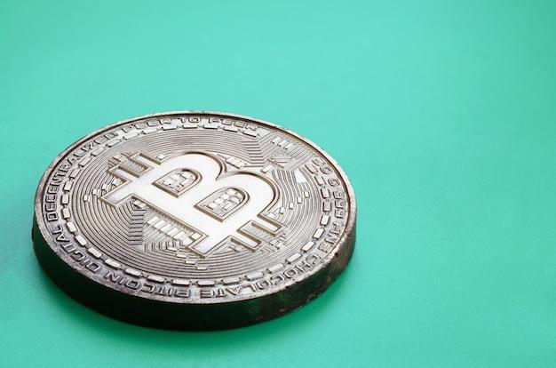 Le produit au chocolat sous forme de bitcoin physique repose sur un fond en plastique vert.