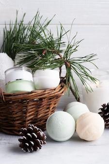 Produit de beauté dans le panier en composition spa de noël avec des branches de pin et de l'huile essentielle, bougie allumée
