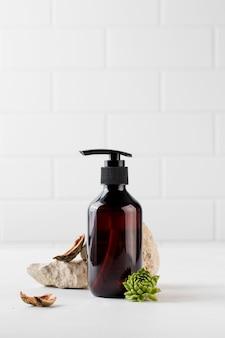 Produit cosmétique biologique dans un distributeur marron entouré de matériaux naturels et respectueux de l'environnement.