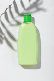 Produit cosmétique dans un tube vert avec un espace vide pour l'étiquette de marque. cosmétiques naturels pour les soins de la peau et des cheveux. shampooing ou lotion à l'ombre des feuilles sur fond blanc