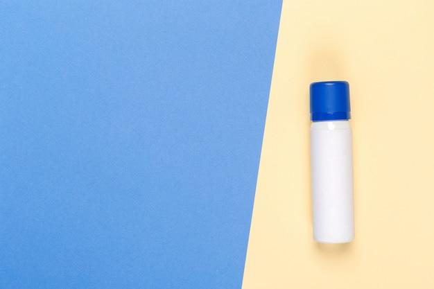 Produit cosmétique sur un fond bicolore lumineux, vue de dessus
