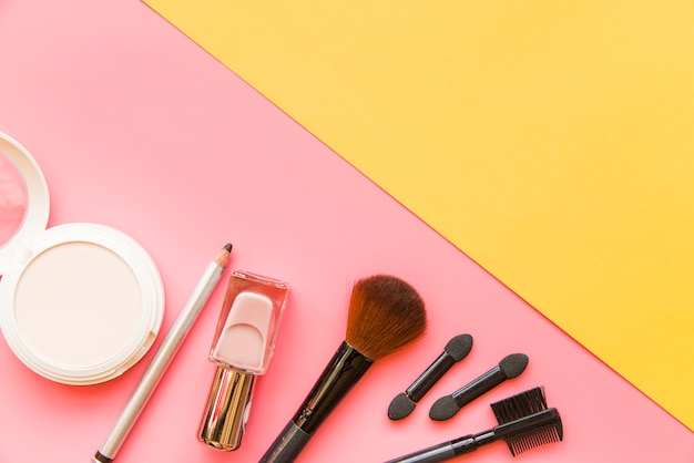 Produit cosmétique avec des pinceaux sur fond double rose et jaune