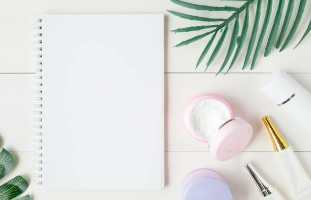 Produit cosmétique et de soin de la peau, cahier et feuilles sur la table