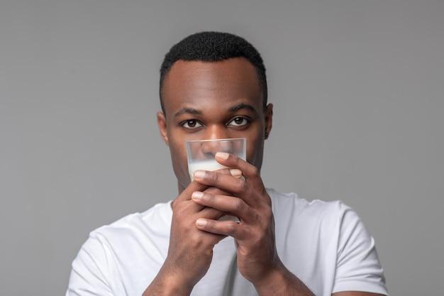 Produit laitier. mignon jeune afro-américain en tshirt blanc tenant un verre de lait au niveau du visage debout sur fond gris clair