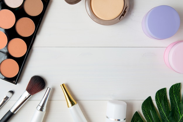 Produit de maquillage, de soin de la peau et de feuilles sur une table en bois blanc