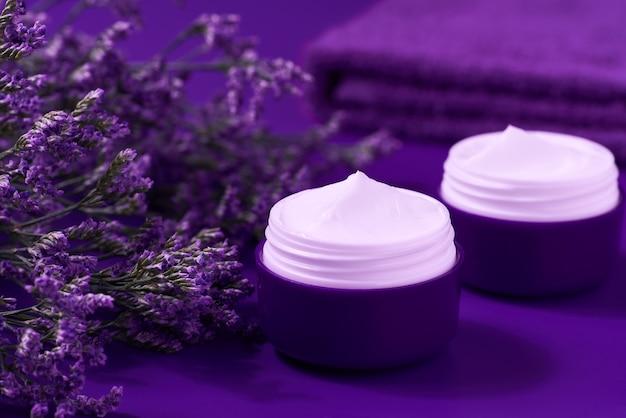 Produit de soin crème hygiénique de nuit dans un pot en plastique violet avec une serviette sur la table. crème cosmétique nettoyante pour la peau ou lotion spa vitaminée, un hydratant anti-rides à base de plantes biologique naturel.