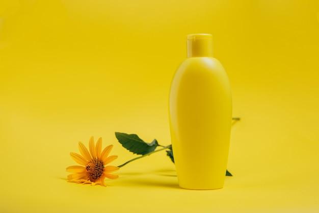 Produit de soin du corps et une fleur sur jaune