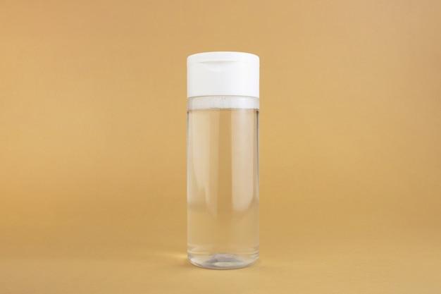 Produit de soin sur fond beige. nettoyant pour le visage ou bouteille d'eau micellaire.