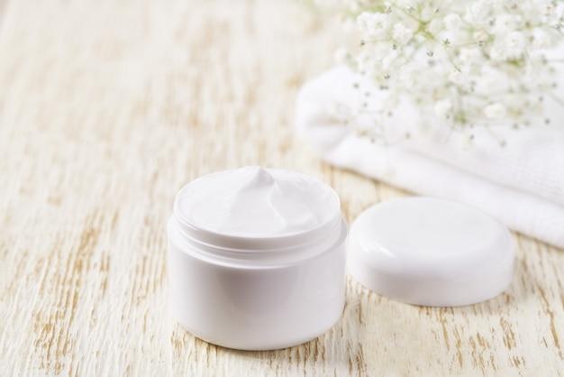 Produit de soin de la peau crème hygiénique dans un pot en plastique avec une serviette sur un tableau blanc. crème cosmétique nettoyante pour la peau ou lotion spa vitaminée, un hydratant anti-rides à base de plantes biologique naturel.