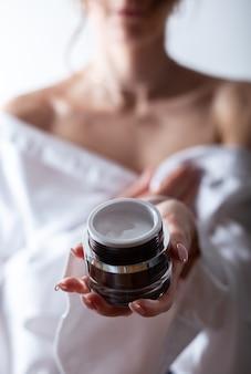 Produit de soin de la peau. gros plan des mains des femmes tenant un pot de crème pour le visage. produit de beauté et spa.