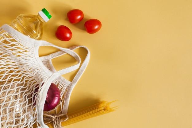 Produits alimentaires dans un sac de ficelle sur une surface jaune avec un espace pour le texte