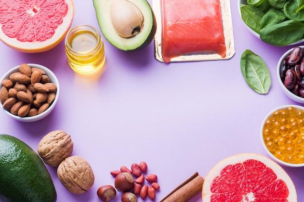 Produits antioxydants pour aliments sains: poisson et avocat, noix et huile de poisson, pamplemousse sur fond rose. espace de copie