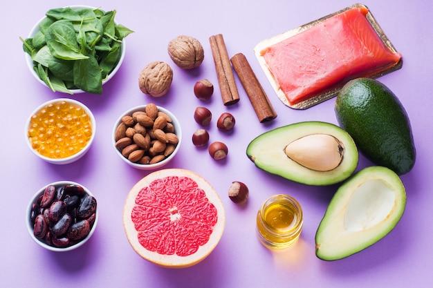 Produits antioxydants pour aliments sains: poisson et avocat, noix et huile de poisson, pamplemousse sur fond rose.