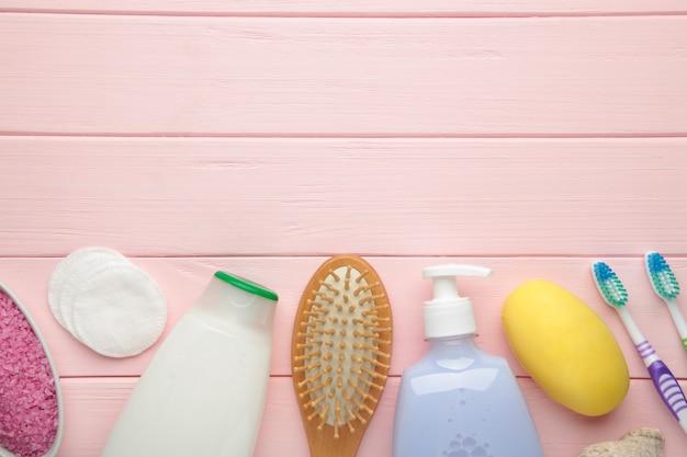 Produits de bain sur mur rose avec espace de copie. gel douche avec sel aromatique, savon et autres articles de toilette.