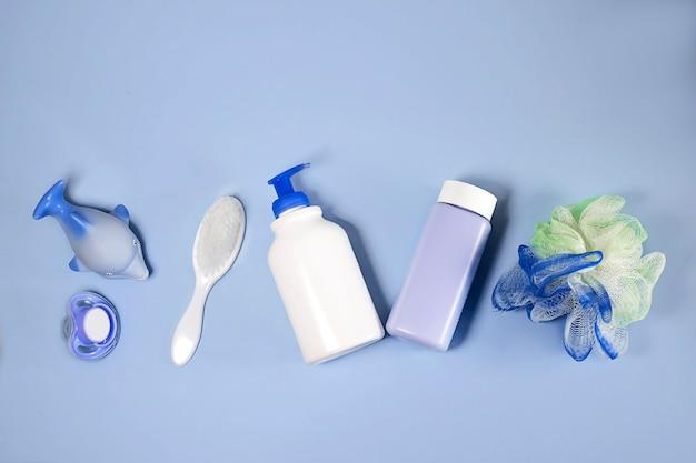 Produits de bain à plat. vue de dessus des articles de bain pour enfants : shampoing, poudre, peigne, éponge, tétine.