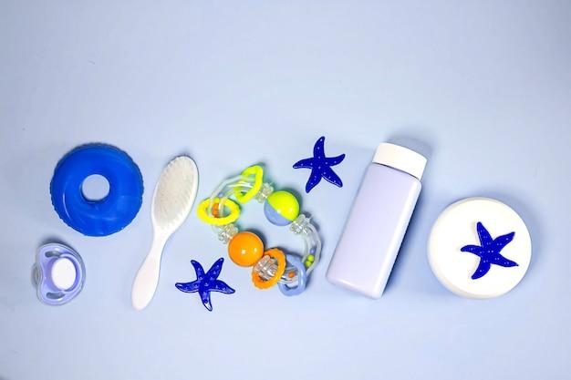 Produits de bain à plat. vue de dessus des objets de bain pour enfants : poudre, peigne, tétine, crème, hochet, jouet étoile de mer. accessoires de lavage de bébé. soins bébé. articles pour nouveau-né.
