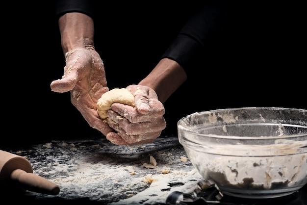 Produits à base de farine gros plan des mains du jeune homme faisant cuire la boulangerie et pétrir la pâte tout en travaillant comme chef.