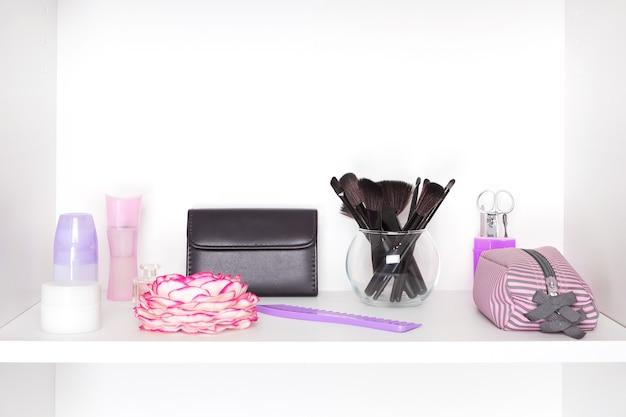 Produits de beauté et accessoires sur étagère blanche à l'intérieur du placard rangement cosmétique et maquillage