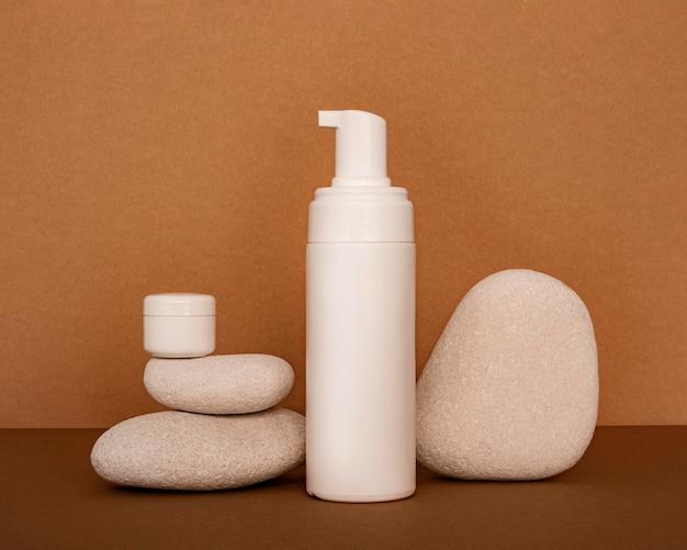Produits de beauté en assortiment de récipients sur pierres beiges