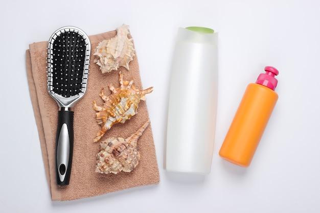 Produits de beauté pour le bain. bouteille de shampoing, coquillages, serviette, brosse à cheveux sur blanc