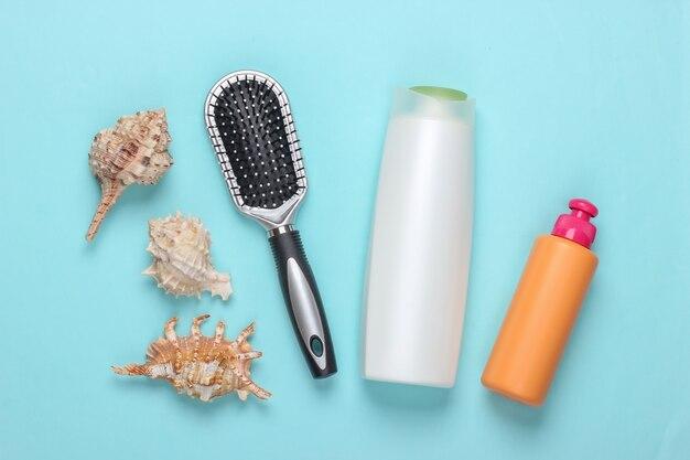 Produits de beauté pour le bain. bouteille de shampoing, coquillages, serviette, brosse à cheveux sur fond bleu. soin des cheveux
