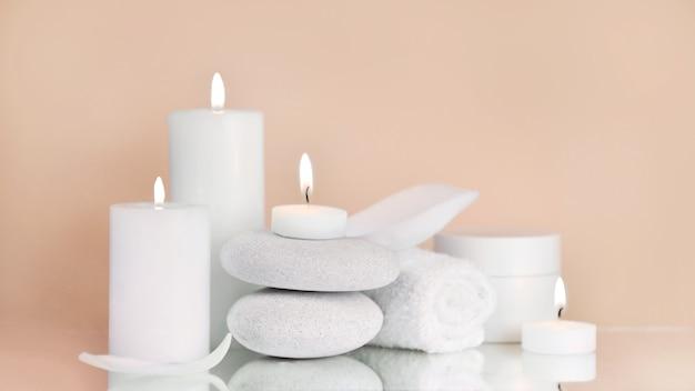 Produits de beauté avec serviette, bougies et pierre blanche